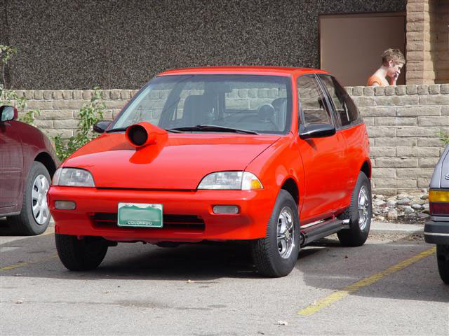 It's a Geo Metro!  With a hood scoop!  Why?!?  Why not!  Awsome...  Sadly, this particular car isn't an EV, but if it was it would have made the hood scoop that much better.